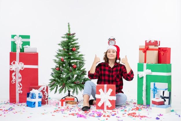 Вид спереди молодой женщины, сидящей вокруг подарков, держащей часы на голове на белой стене