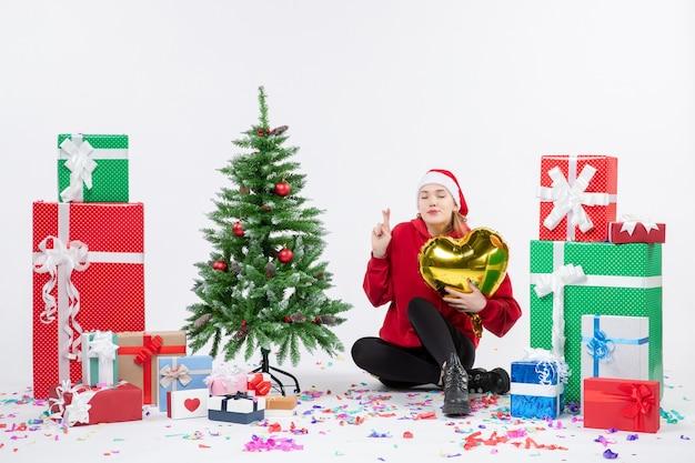Вид спереди молодой женщины, сидящей вокруг подарков, держащей фигуру золотого сердца на белой стене