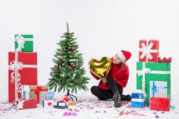 白い壁に金のハートの図を保持しているプレゼントの周りに座っている若い女性の正面図
