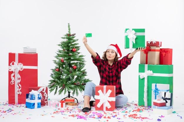 緑の銀行カードを保持し、白い壁に存在するプレゼントの周りに座っている若い女性の正面図