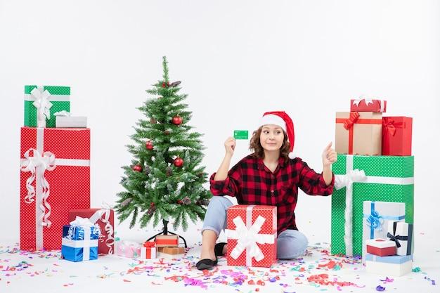 白い壁に緑の銀行カードを保持しているプレゼントの周りに座っている若い女性の正面図