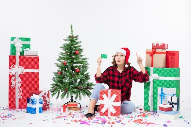 Вид спереди молодой женщины, сидящей вокруг подарков, держащей зеленую банковскую карту на белой стене