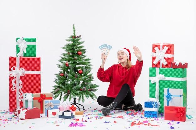 Вид спереди молодой женщины, сидящей вокруг подарков, держа билеты на самолет на белой стене