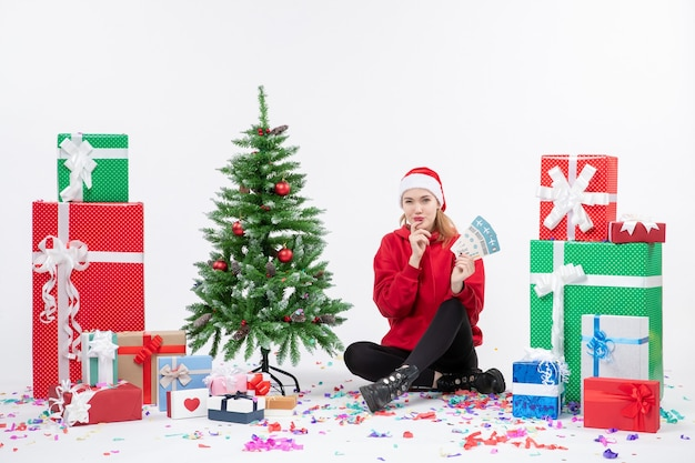 흰 벽에 비행기 티켓을 들고 선물 주위에 앉아있는 젊은 여자의 전면보기