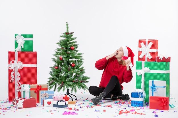 흰 벽에 빨간 은행 카드를 들고 선물 주위에 앉아있는 젊은 여자의 전면보기
