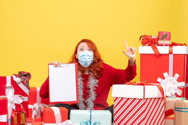 Вид спереди молодой женщины, сидящей вокруг подарков в маске с файловой заметкой на желтой стене