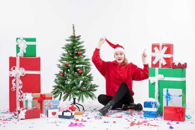 흰 벽에 선물 주위에 앉아 젊은 여자의 전면보기