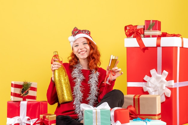 크리스마스 선물 주위에 앉아 노란색 벽에 샴페인으로 축하하는 젊은 여자의 전면보기