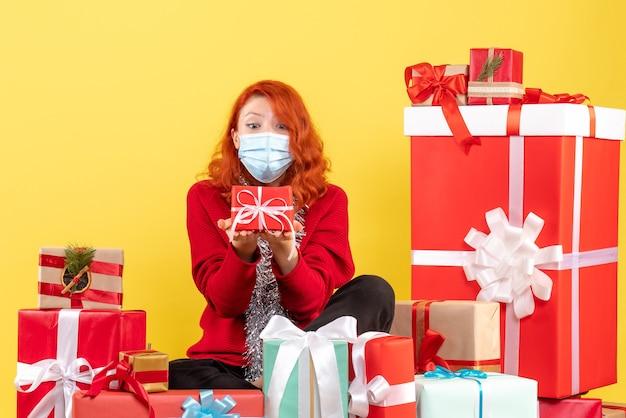 クリスマスの周りに座っている若い女性の正面図は黄色の壁にマスクで提示します