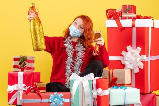 크리스마스 주위에 앉아있는 젊은 여자의 전면보기 노란색 벽에 샴페인 마스크에 선물
