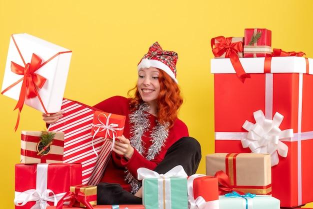 黄色の壁にクリスマスプレゼントの周りに座っている若い女性の正面図