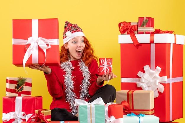 크리스마스 주위에 앉아있는 젊은 여자의 전면보기 노란색 벽에 선물