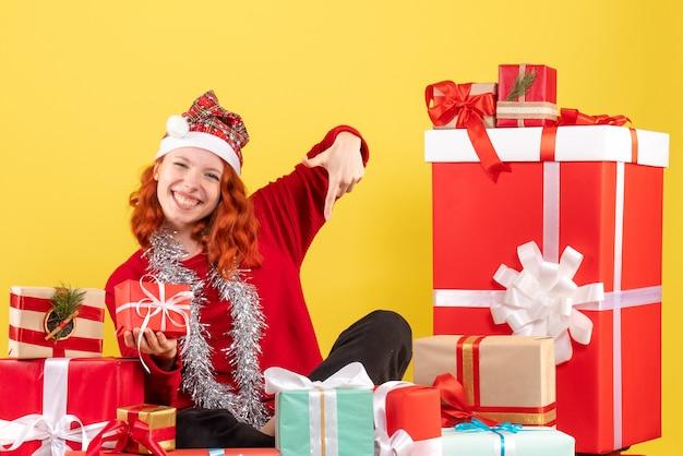 Вид спереди молодой женщины, сидящей вокруг рождественских подарков на желтой стене