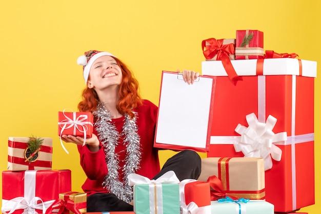Вид спереди молодой женщины, сидящей вокруг рождественских подарков с файловой заметкой на желтой стене