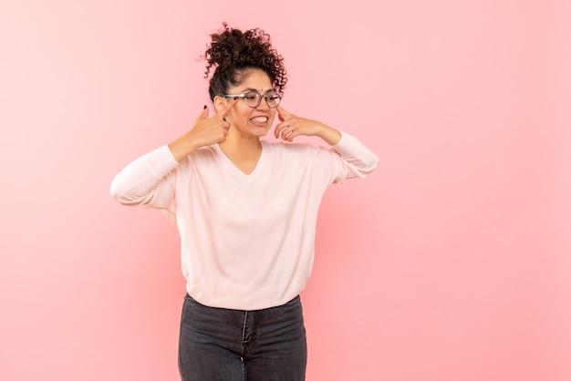 분홍색 벽에 웃 고 젊은 여자의 전면보기