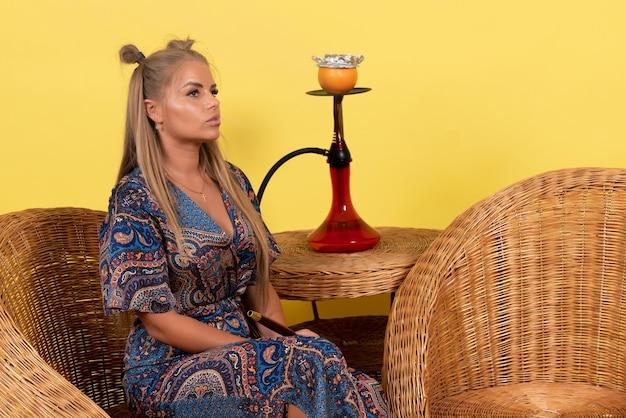 노란색 벽에 물담배를 피우는 젊은 여성의 전면 모습
