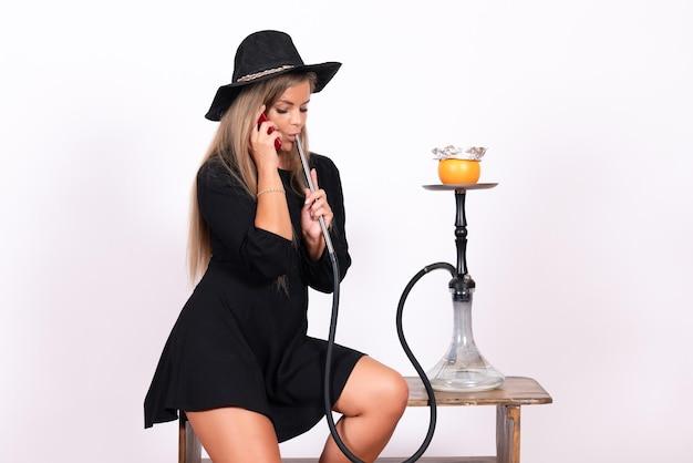 흰 벽에 물담배를 피우는 젊은 여성의 전면 모습 무료 사진
