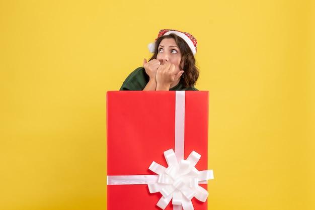 노란색 벽에 상자 안에 서있는 젊은 여자의 전면보기