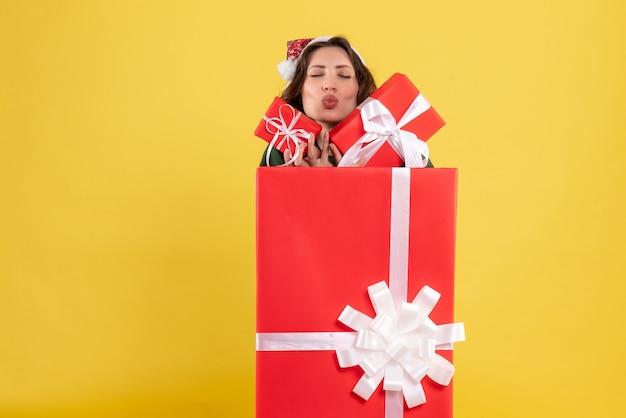 Вид спереди молодой женщины, стоящей внутри коробки с рождественскими подарками на желтой стене