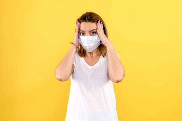 黄色の壁にマスクで強調された若い女性の正面図