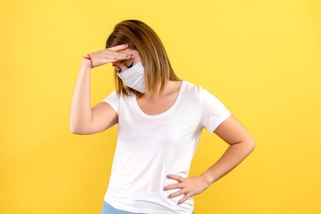 Вид спереди молодой женщины, подчеркнутой в маске на желтой стене