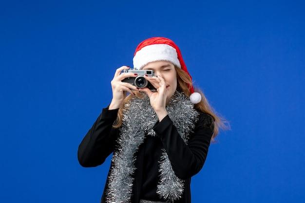 파란색 벽에 카메라로 사진을 찍는 젊은 여성의 전면 모습