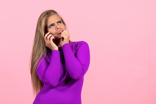 밝은 분홍색 벽에 아름다운 보라색 드레스를 입고 전화 통화를 하는 젊은 여성의 전면 보기