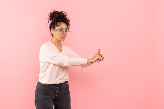 Вид спереди молодой женщины, разговаривающей с кем-то на розовой стене