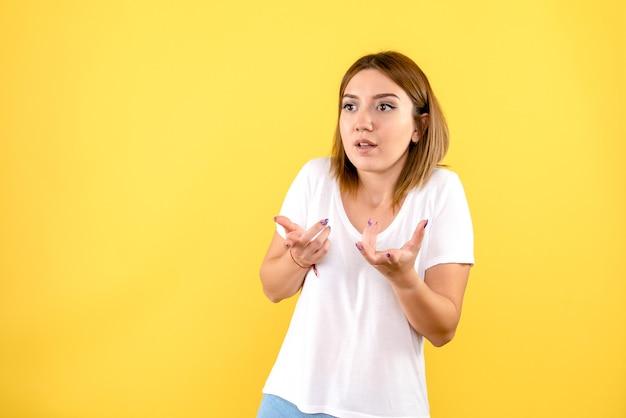Вид спереди молодой женщины, разговаривающей с кем-то на желтой стене