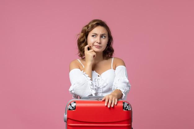 분홍색 벽에 빨간 가방을 들고 여행을 준비하고 생각하는 젊은 여성의 전면