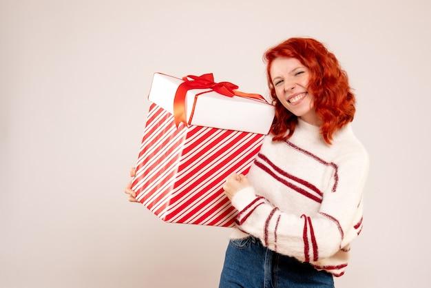 Вид спереди молодой женщины с большим подарком на белой стене