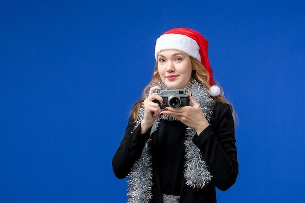 青い壁にカメラを持つ若い女性の正面図
