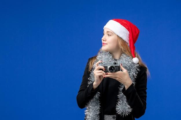 파란 벽에 카메라를 든 젊은 여성의 전면 모습