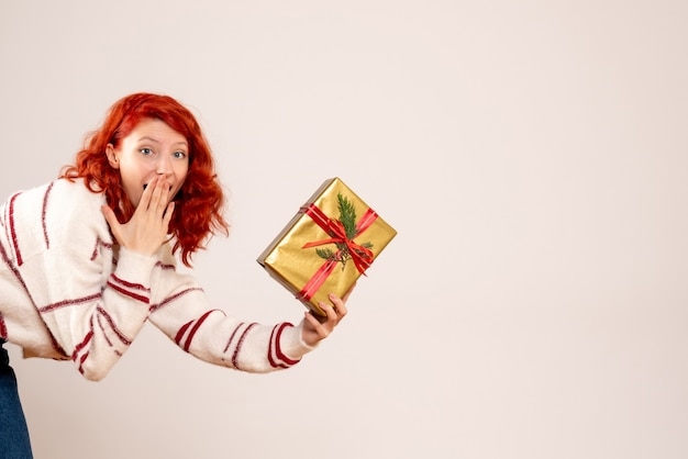 Вид спереди молодой женщины с рождественским подарком на белой стене