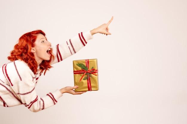 흰 벽에 크리스마스 선물을 가진 젊은 여자의 전면보기