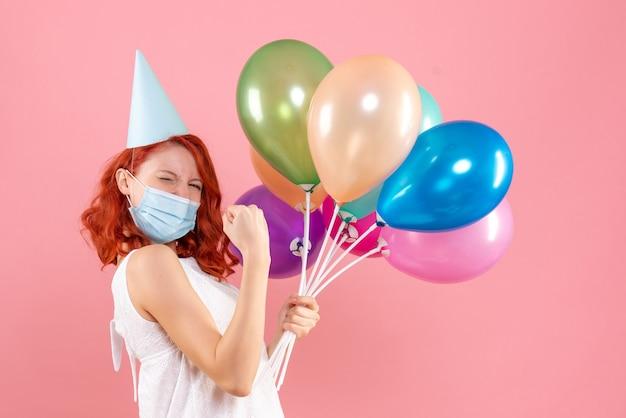 ピンクの壁に滅菌マスクでカラフルな風船を持つ若い女性の正面図