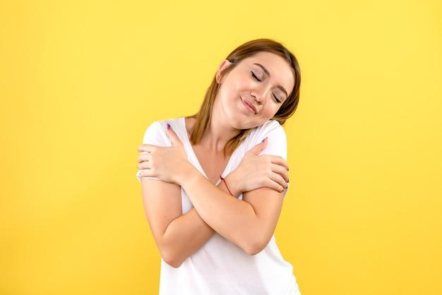 노란색 벽에 기쁘게 얼굴을 가진 젊은 여자의 전면보기