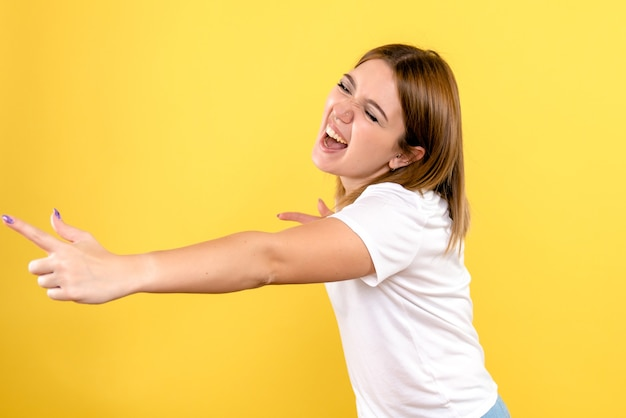노란색 벽에 감정적 인 얼굴을 가진 젊은 여자의 전면보기