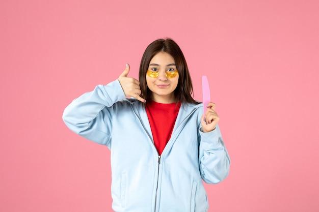 ピンクの壁に眼帯と爪やすりで若い女性の正面図