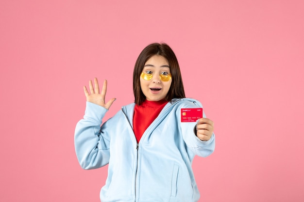 분홍색 벽에 은행 카드를 들고 있는 눈 패치를 가진 젊은 여성의 전면