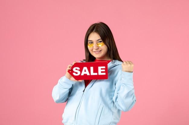 분홍색 벽에 판매 배너를 들고 안대를 가진 젊은 여성의 전면 보기
