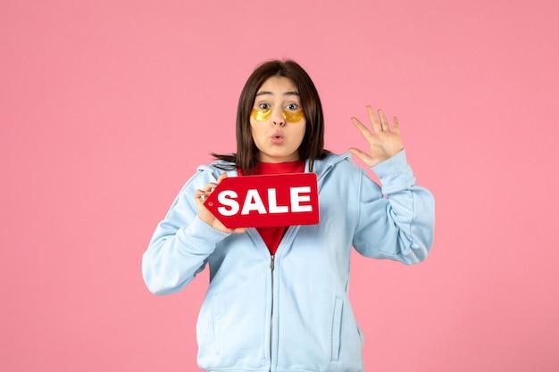 ピンクの壁に販売バナーを保持している眼帯を持つ若い女性の正面図