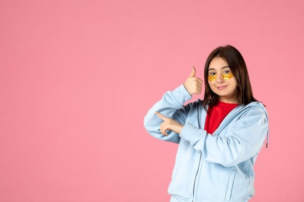분홍색 벽에 눈 패치가 있는 젊은 여성의 전면 모습