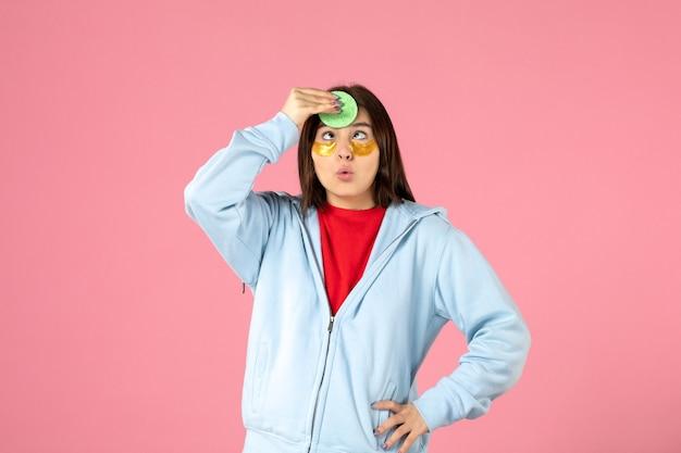 ピンクの壁に彼女の顔の皮膚の世話をしている眼帯を持つ若い女性の正面図