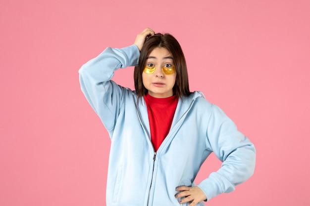 ピンクの壁に彼女の目の下に眼帯を持つ若い女性の正面図