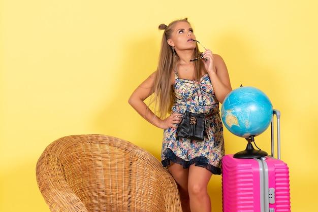Вид спереди молодой женщины с глобусом и розовой сумкой на летних каникулах на желтой стене