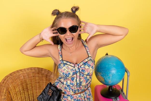 黄色の壁にポーズをとって夏休みの地球とピンクのバッグを持つ若い女性の正面図