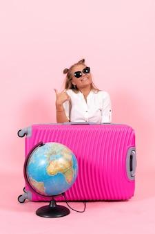 핑크색 가방을 들고 휴가를 준비하는 젊은 여성의 앞모습은 분홍색 벽에 행복감을 느낀다