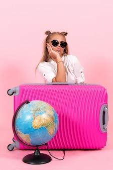 ピンクの壁に休暇の準備をしている彼女のピンクのバッグを持つ若い女性の正面図
