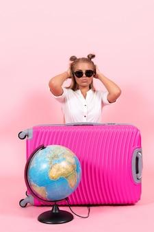 분홍색 벽에 휴가를 준비하는 분홍색 가방을 든 젊은 여성의 전면